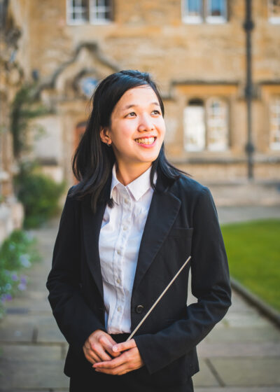Malaysian Chinese conductor (she/her) holding her baton at Oriel College, Oxford